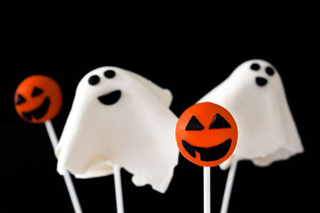 phantom: With Halloween cake pops phantom and pumpkin shape on black background Stock Photo