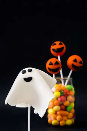 cake pops: Halloween cake pops and colored candies on black background