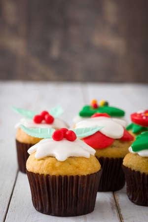 christmas cupcakes: Christmas cupcakes on white wooden table Stock Photo