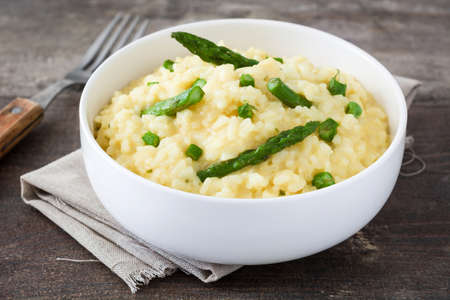 Risotto with asparagus and peas on wood Imagens