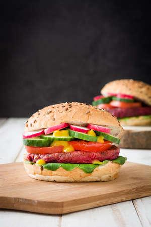 vegetarian hamburger: Veggie burger beet on a white wooden table and black background