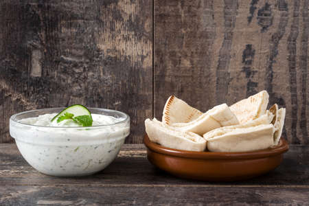 tzatziki: Tzatziki sauce and pita bread on rustic wooden background Stock Photo