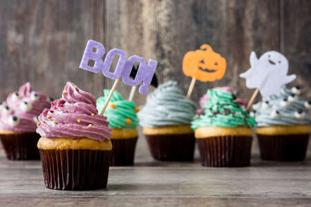 Halloween cupcakes and cobweb on rustic wooden background