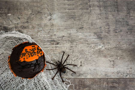 wood spider: Halloween muffin and a spider on rustic wooden background
