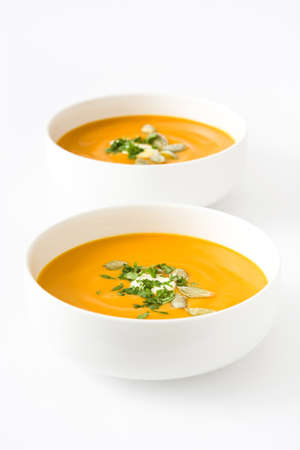 Pumpkin soup with cream and pumpkin seeds isolated on white background