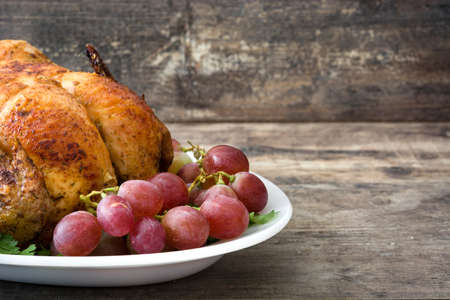 garnished: Garnished roasted turkey with grapes and herbs on a wooden table
