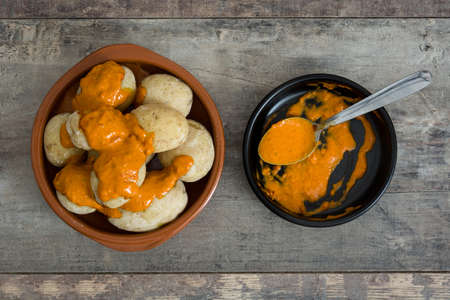 mojo: Canarian potatoes (boiled potatoes) With wet sauce on wooden table