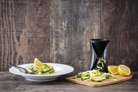Zucchini noodles with pesto sauce on wooden table