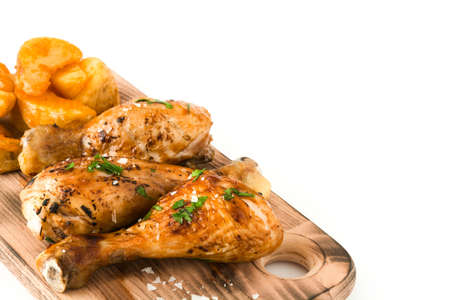 Roast chicken drumsticks on cutting board and chips isolated on white background