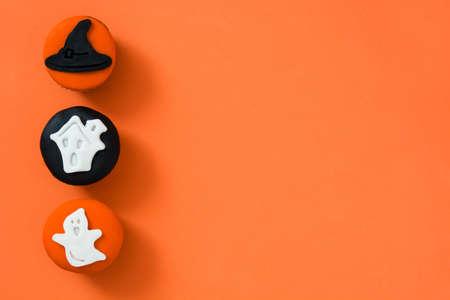 Halloween cupcakes on orange background
