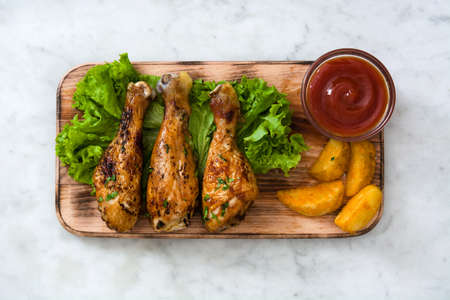 plates of food: Roast chicken drumsticks and chips on white marble