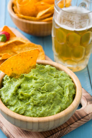 Nachos, guacamole and beer on blue wooden table Imagens - 64271432