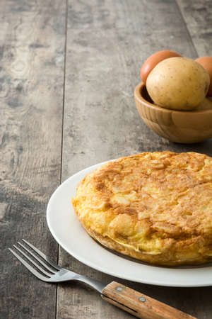 Traditional spanish omelette with potatoes and eggs on wooden table