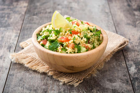 Tabbouleh salad with couscous in bowl on rustic table Imagens - 64271688
