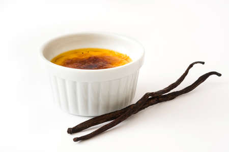 Creme brulee and vanilla pods, isolated on white background. Stock Photo