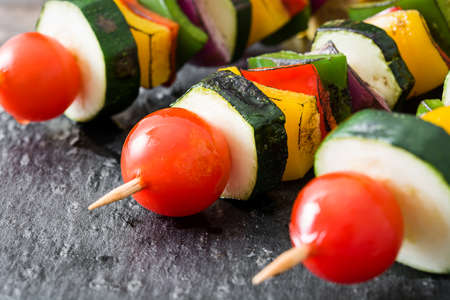 Vegetable skewers on slate plate and wooden table