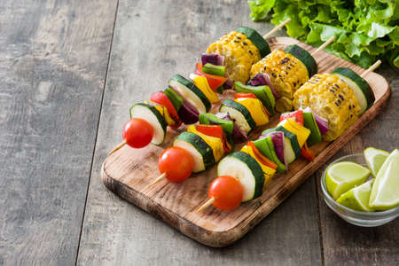 Vegetable skewers on wooden table Stock Photo