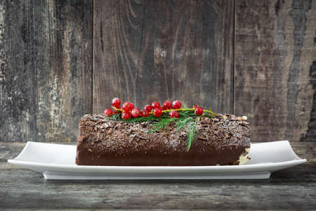 yule: Chocolate yule log cake with red currant on wooden background