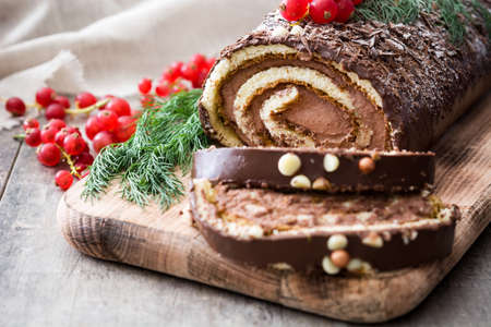Christmas chocolate yule log cake with red currant on wooden background.closeup
