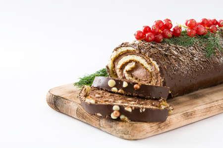 Weihnachtsschokoladen-Julblock-Kuchen mit der roten Johannisbeere lokalisiert auf weißem Hintergrund Standard-Bild - 66137325