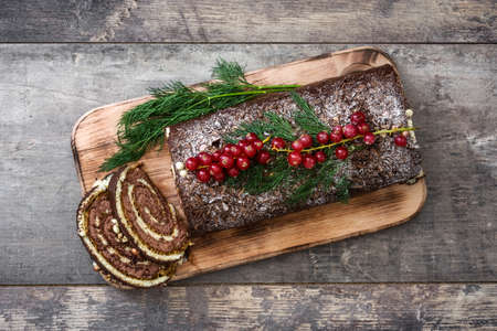 yule: Christmas chocolate yule log cake with red currant on wooden background.copyspace