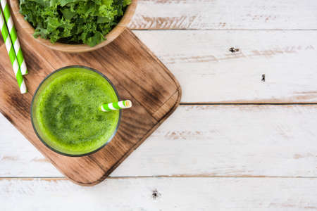 copyspace: Kale smoothie in glass on white wooden background.Top view Stock Photo