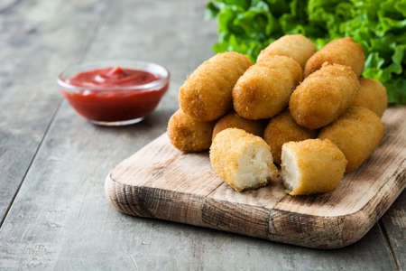 Traditional Spanish fried croquetas (croquettes) With ketchup on wooden background Фото со стока