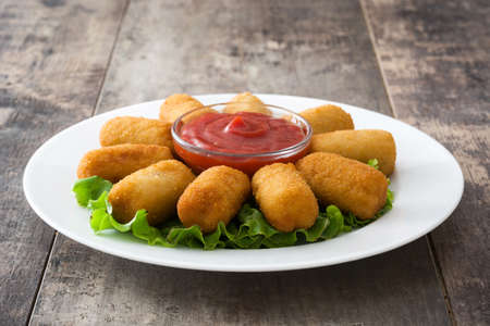 Traditional Spanish fried croquetas (croquettes) With Ketchup in plate on wooden background Imagens - 68894136