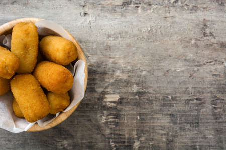 Traditional Spanish fried croquetas (croquettes) in plate on wooden background Archivio Fotografico