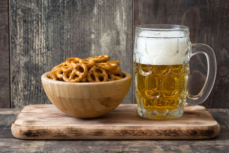 Pretzels and beer in bowl on wooden table