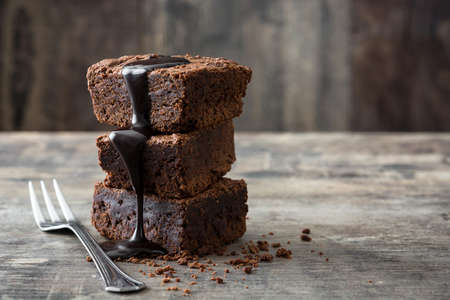 Chocolate brownie with chocolate syrup on wooden background