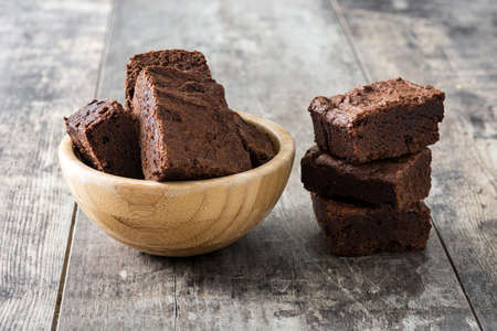 Chocolate brownie portions in bowl on wooden background Stock Photo