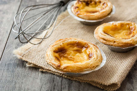 Pasteis de nata. Typical Portuguese egg custard tart on wooden background Banco de Imagens