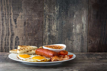 bacon baked beans: Traditional full  English breakfast with fried eggs, sausages, beans, mushrooms, grilled tomatoes and bacon on wooden background