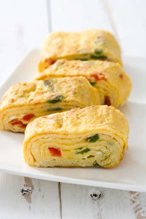 Tamagoyaki Traditional Japanese omelette on white wooden table.