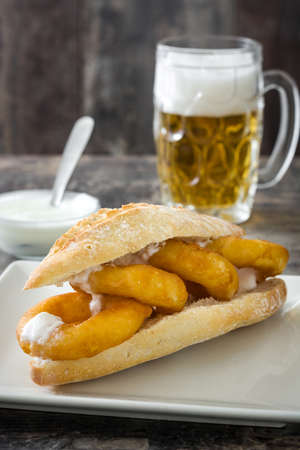 Calamari sandwich and beer on wooden table