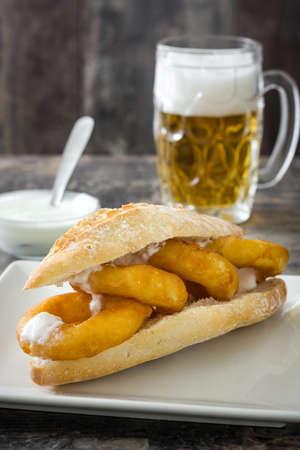Calamari Sandwich und Bier auf Holztisch Standard-Bild - 69603225