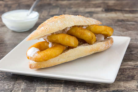 Calamari sandwich with aioli on wooden table Standard-Bild