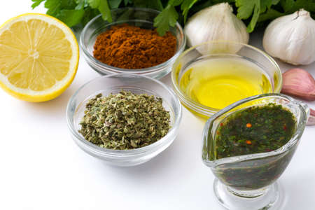 Green Chimichurri Sauce and ingredients isolated on white background Stock Photo