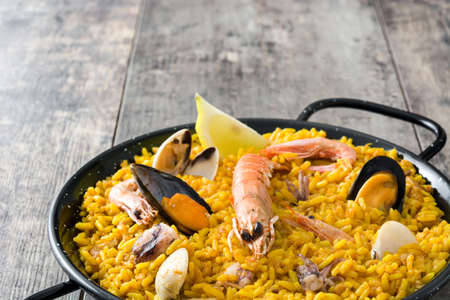 mussel: Traditional Spanish seafood paella on wooden background Stock Photo