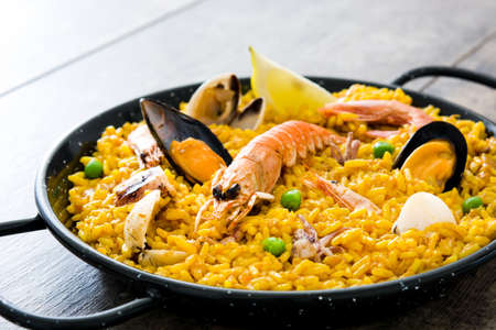 Traditional Spanish seafood paella on wooden background Foto de archivo