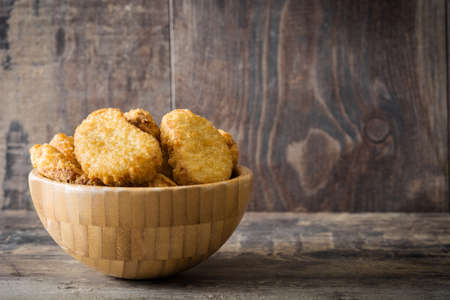 Fried chicken nuggets in bowl on wooden table