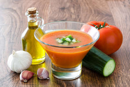 Traditional Spanish cold gazpacho soup and ingredients on wooden table
