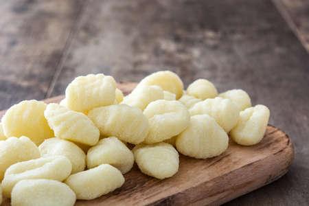 Uncooked potato gnocchi on wooden table Stock Photo