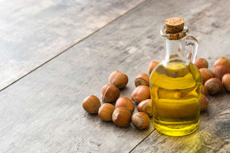Hazelnuts oil in a bottle on wooden table background
