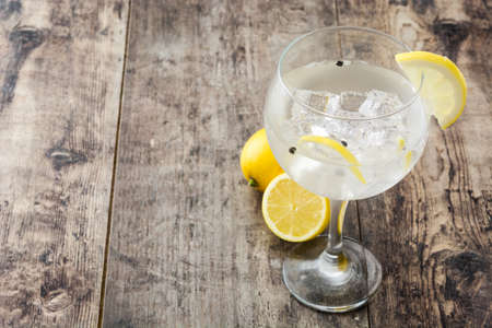 Glass of gin and tonic with lemon on wooden background.Copyspace Imagens