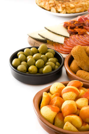 Traditional spanish tapas. Croquettes, olives, ham and potatoes isolated on white background