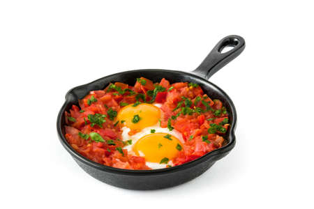 Shakshuka in iron frying pan isolated on white background. Typical food in Israel.
