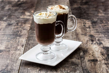 Irish coffee in glass on wooden background