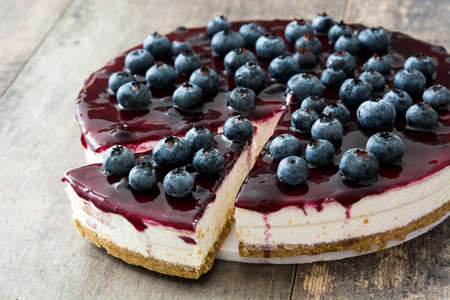 Blueberry cheesecake on wooden table Imagens